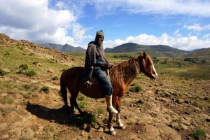 Foto di un uomo basotho  a cavallo in Lesotho.