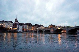 Foto del Reno a Basilea in tarda serata con le luci riflesse nell'acqua.