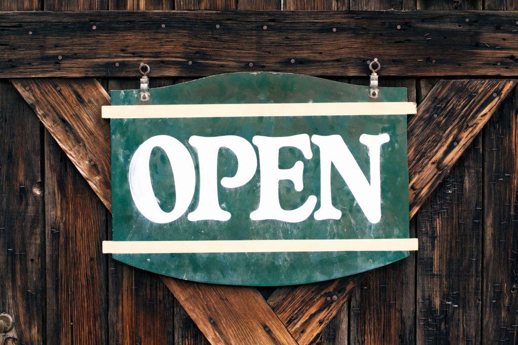 """Foto di un cartello su una porta con scritto """"open""""."""