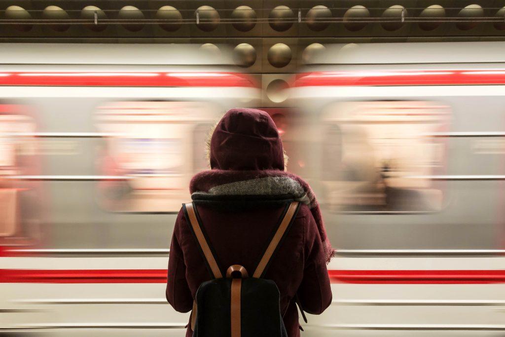 Foto di una ragazza davanti a un treno in movimento.