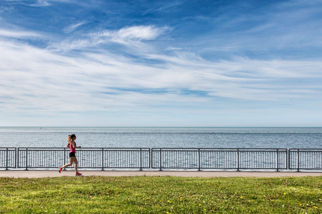 Fotografia di una ragazza che corre sul lungomare.