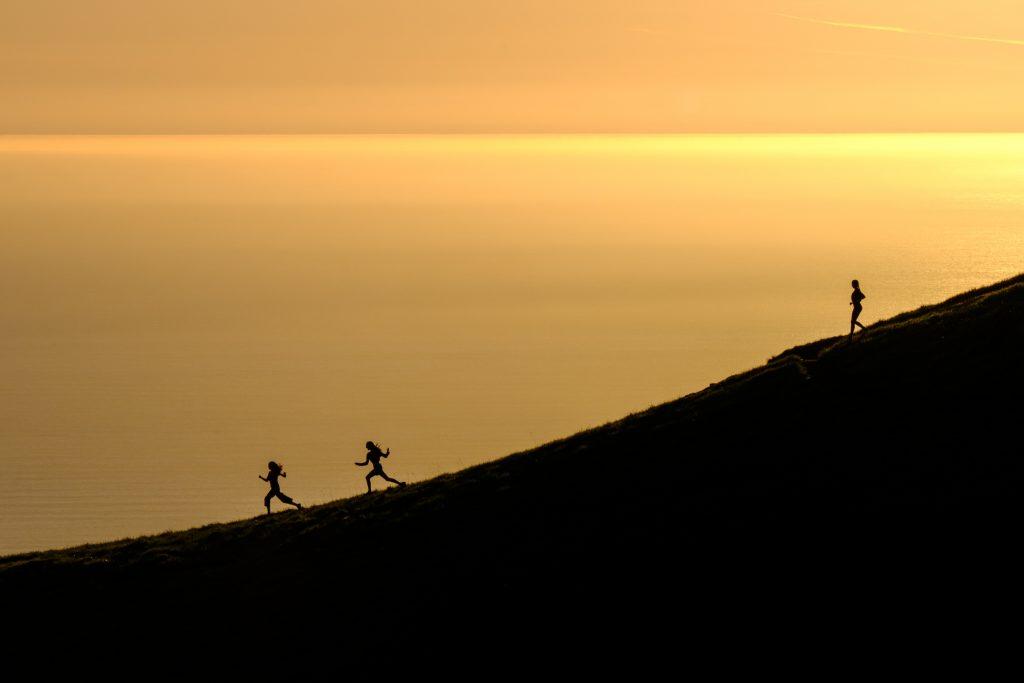 Fotografia di tre persone che corrono al tramonto.
