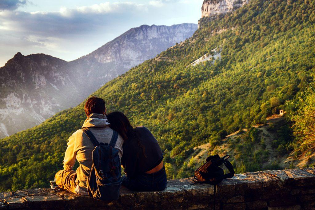 Foto di una coppia di fronte a delle montagne.