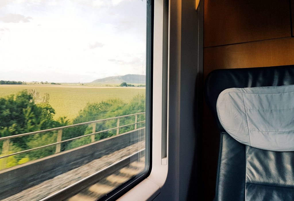 Foto di un paesaggio scattata dal finestrino di un treno in movimento.