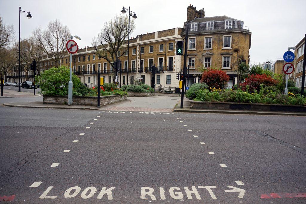 """Foto di una strada con la scritta """"look right""""."""
