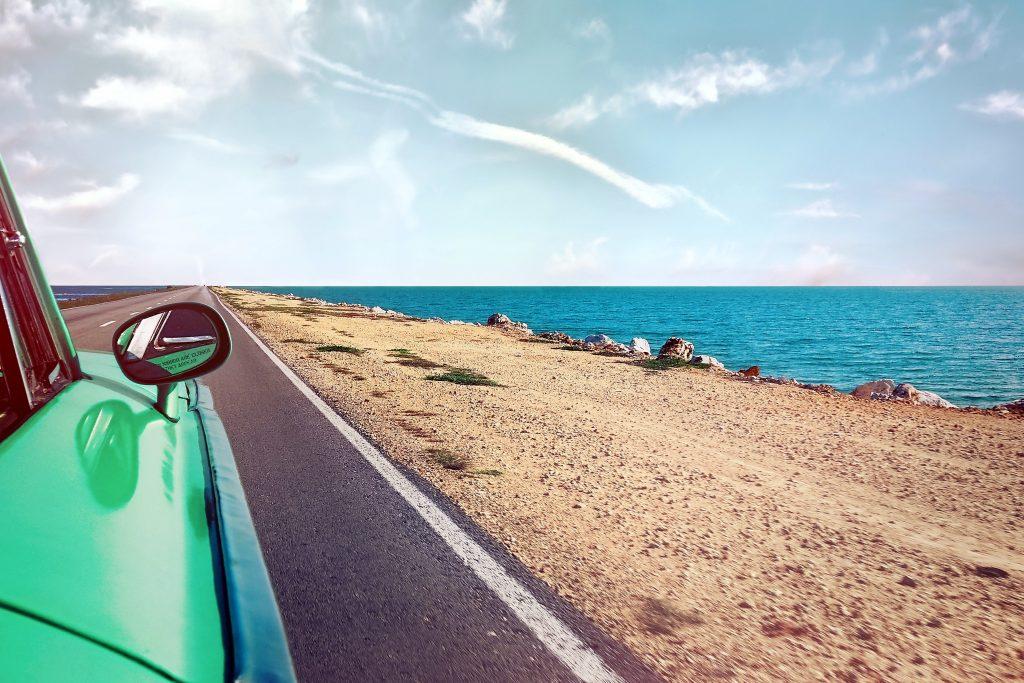 Fotografia di una macchina in una strada con vicino il mare.