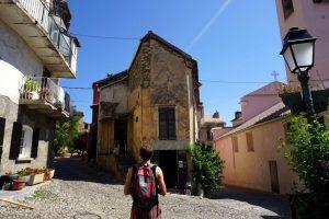 Fotografia di una viuzza e casa con mura scrostate a Corte, Corsica.