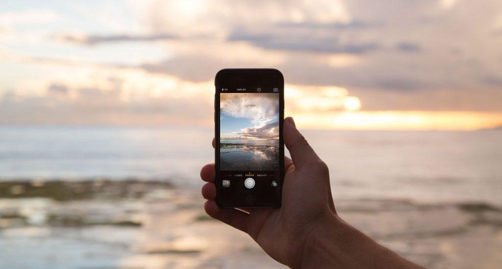 Foto di un telefono mentre viene scattata una fotografia al tramonto.