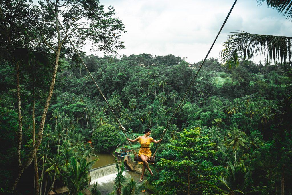 Foto di una ragazza su un'altalena sospesa nella giungla di Bali.