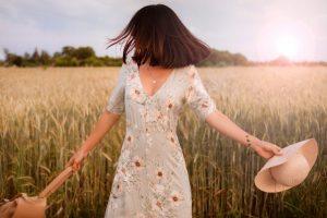 Foto di una ragazza in un campo di grano con un capello in mano.